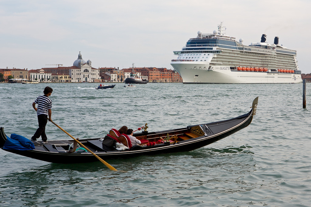 Contrasting a gondola and a cruise ship cruising along the grand canal in Venice.