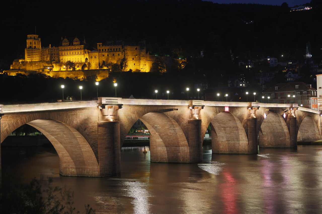 Lights from the bridge reflect off of the river, with Heidelberg castle in the background.