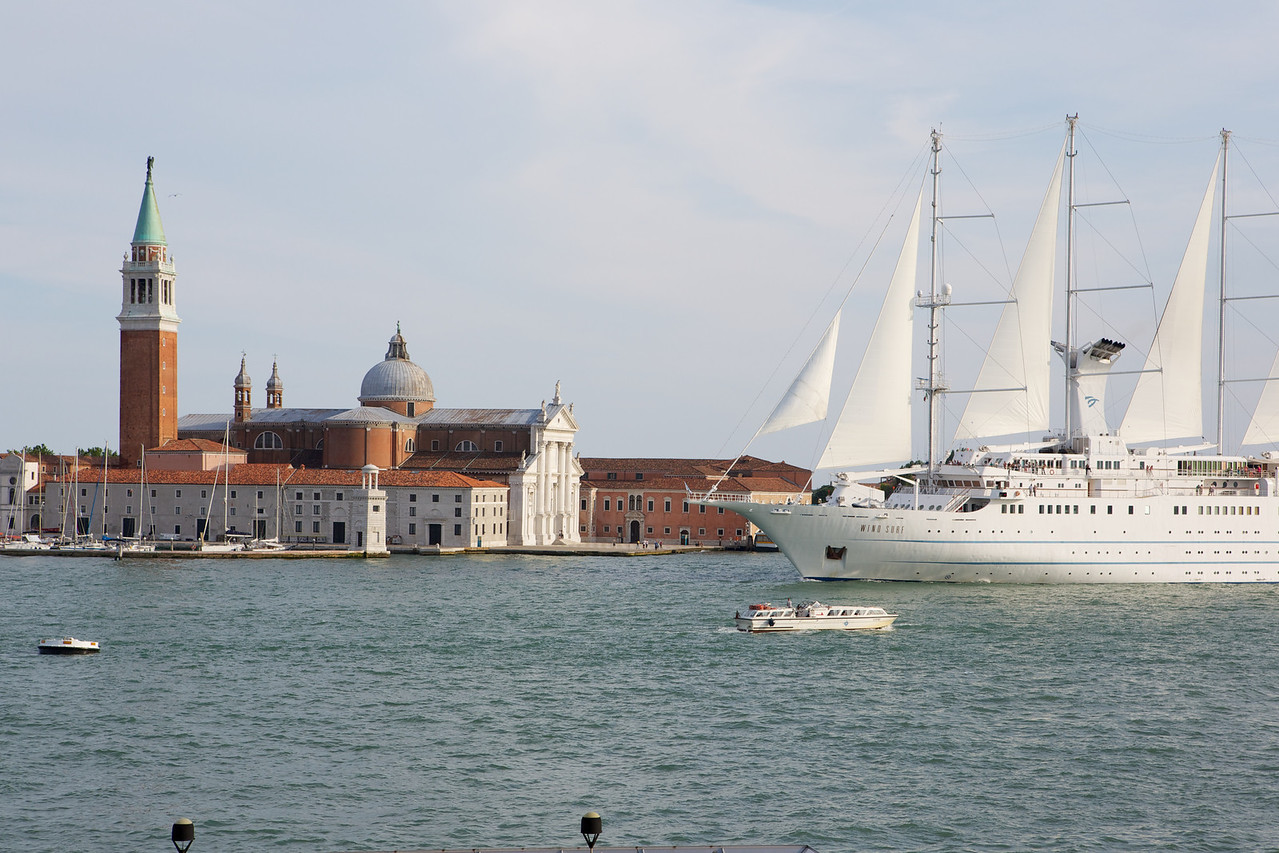 A large modern sailing ship crosses in front of an old world church in Venice.