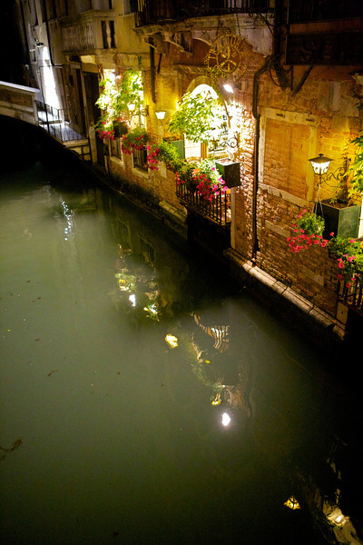 The side of a restaurant in Venice at night.  The canal water isn't particularly clear, but I suppose its all part of the charm.