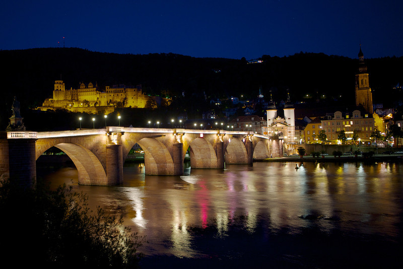 The Neckar river, Heidelberg castle, and Heidelberg cathedral at night.
