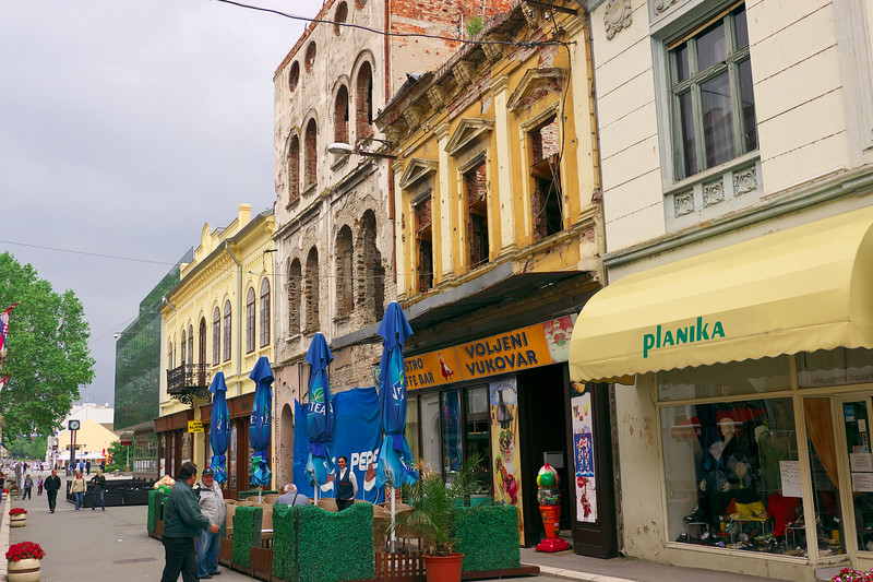 Restored buildings next to some unrepaired buildings. The secong building from the right has the first floor repaired but not the second floor.