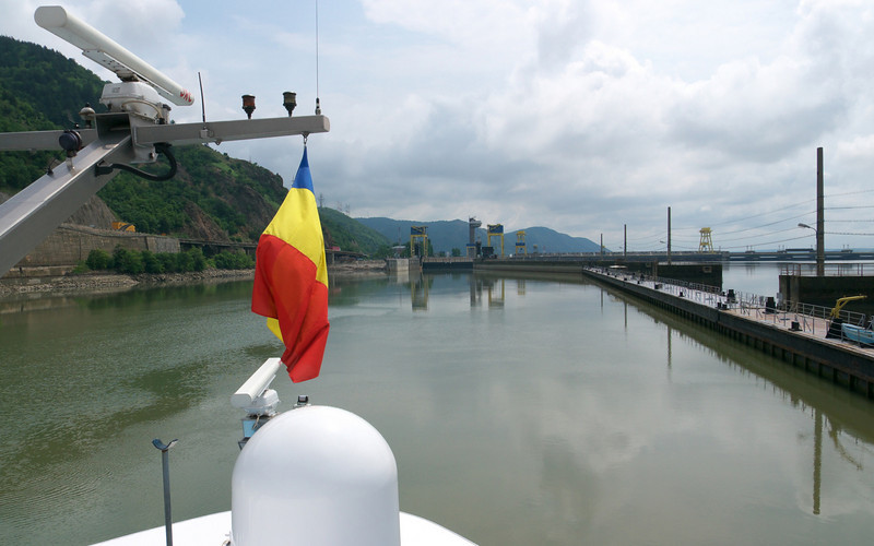 The ship always flies the flag of the country in which it is sailing. In this case we are on the Romanian side so a Romanian flag. When we are sailing in the middle of the channel, the ship does not fly a country flag.