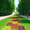 A large park with flower beds, walking paths and a Soviet era statue at the end.