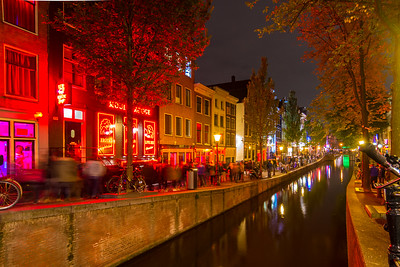 A truly red area of the Red Light District. There's a woman working in the pink window on the left.