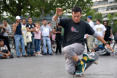 "A urban skater is performing in Berlin; on his t-shirt, ""no-limit"""