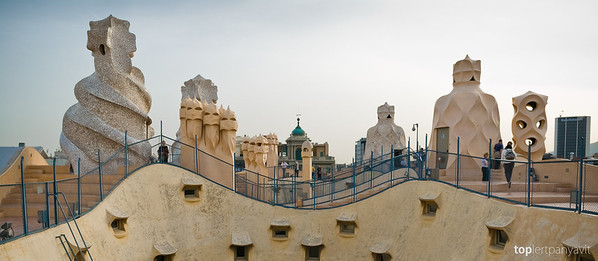 Strange sculptures stand on top of Casa Mila by Antonia Gaudi in Barcelona