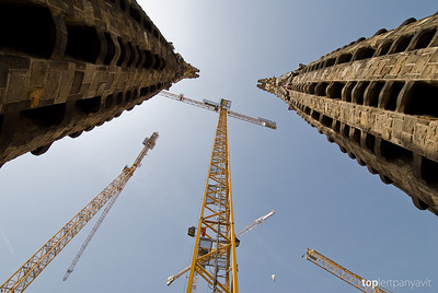 Construction cranes stand with the towers of the Sagrada Familia church in Barcelona