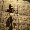 Silhouette of a man going to work in his bike early in the morning, as shown by its long shadow. Brugge, Belgium.