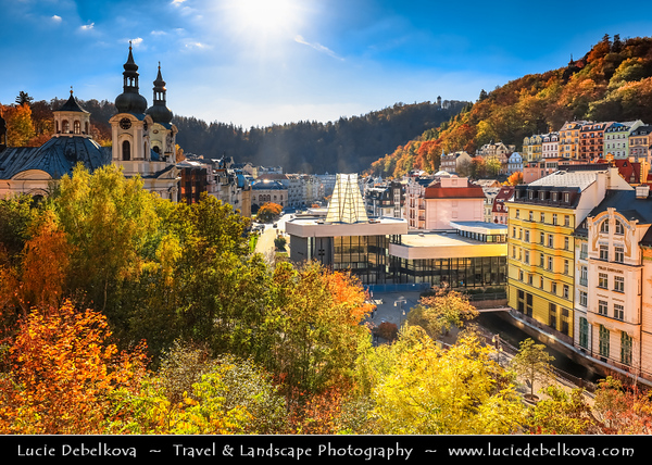 Europe - Czech Republic - Czechia - Karlovy Vary - Carlsbad - Karlsbad - Spa town on confluence of rivers Ohře & Teplá, named after Charles IV, Holy Roman Emperor & King of Bohemia, who founded city in 1370 - Historically famous for its hot springs (13 main springs, about 300 smaller springs) - Cityscape panorama of historic part with Twin-steeple Catholic Church of St. Mary Magdalene - Kostel Mari Magdaleny & Vridelni kolonada - Vřídelní kolonáda - Thermal hot spring colonnade - Modern glass & reinforced concrete building in Functionalistic style with arches over most popular spring built built between 1969 - 1975