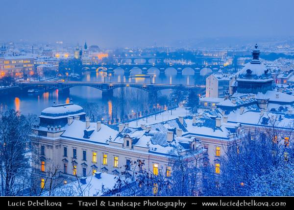 Europe - Czech Republic - Bohemia - Prague - Praha - Historical Centre - Prague Old Town - Staré Město Pražské - UNESCO World Heritage Site - Bridges over the Vltava river under fresh snow during winter at Dusk - Blue Hour - Twilight - Night