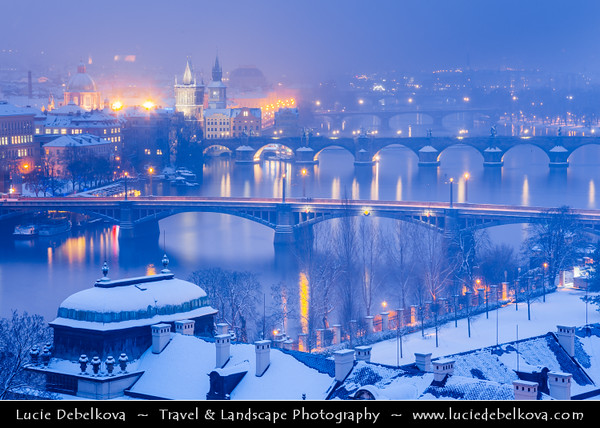 Europe - Czech Republic - Bohemia - Prague - Praha - Historical Centre - Prague Old Town - Staré Město Pražské - UNESCO World Heritage Site - Bridges over the Vltava river under fresh snow during winter at Dusk - Blue Hour - Twilight - Night