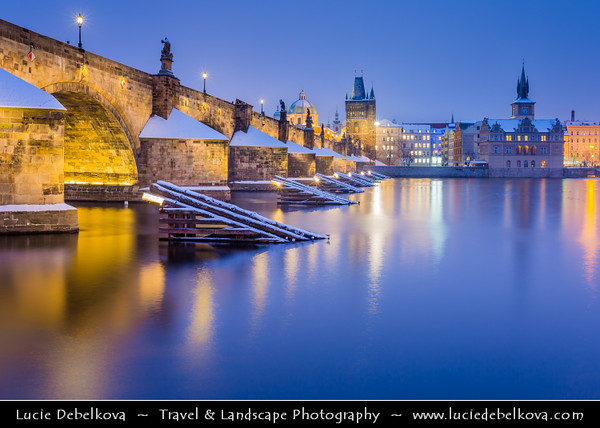 Europe - Czech Republic - Bohemia - Prague - Praha - Historical Centre - Prague Old Town - Staré Město Pražské - UNESCO World Heritage Site - Charles bridges - Karlův Most - One of the most iconic Prague locations over Vltava River under fresh cover of snow at winter Dusk - Blue Hour - Twilight - Night