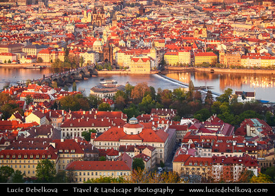 Czech Republic - Prague - Praha - Capital City - Sunset over Historical City Center with many old red roof houses and Charles bridge - Karlův Most - One of the most iconic Prague locations over Vltava River