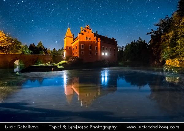 Europe - Czech Republic - Czechia - South Bohemian Region - Červená Lhota Vodní Zámek - Red Lhota Water Château - Iconic red castle standing at middle of lake on rocky island - Night sky with stars