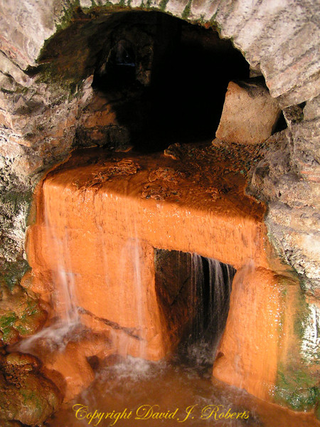 Mineral water flowing from the pipes in the Roman baths in Bath England. The orange is mineral staining of the limestone structures.