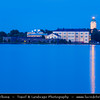 Finland - Helsinki - Helsingfors - Suomenlinna Fortress Lighthouse on the top of a church & Navy academy buildings seen from Kaivopuisto park district across the sea - Dusk - Twilight - Blue Hour - UNESCO World Heritage site