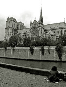 Artist by the seine sketching Notre Dame Cathedral as seen from quai de Montebello