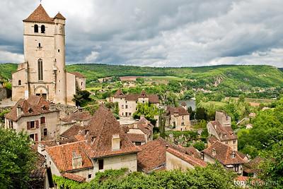 Dark clouds gather around the small French village of Saint-Cirq-Lapopie