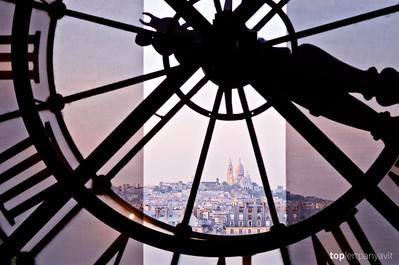 The Basilique du Sacre-Coeur is illuminated by dusk light from the clock tower in the Musee d'Orsay in Paris
