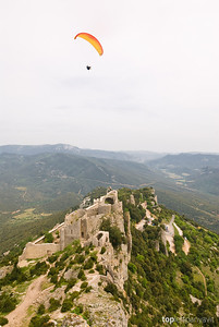 A paraglider catches thermals above the Cathar fortress of Peyrepertuse in the Pyrenees mountains