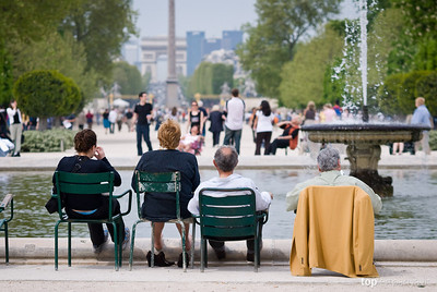 Parisians relax by a fountain at the Jardin de Tuilleries with the Place de Concorde obelisk and the Arc de Triomphe in the distance