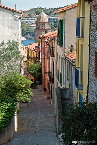 The Notre-Dame-des-Anges church is viewed in the distance from a street alley in Collioure