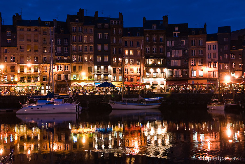 Honfleur harbor bustles with night life and lights