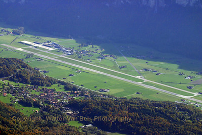"""Aerial view on Meiringen AFB (picture taken from nearby """"Rothorn"""" mountain at 2350m altitude) with beautiful autumn colors. You can clearly understand why they called this mountain (the one in the sun) """"Rothorn"""" (some of the trees have a wonderfull brown-red color, this time of the year)! On the runway are three F-5E's (two from Patrouille Swiss and one in standard grey paint) having just started their take-off roll. The two taxiways leading to the famous shelters (i.e. caverns in the mountain) are also visible."""