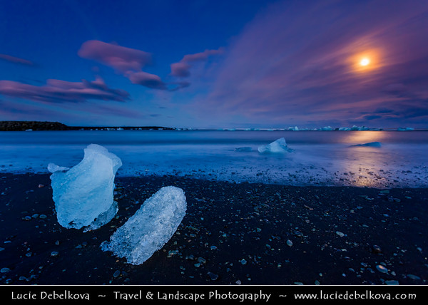 Europe - Iceland - South Eastern Iceland - Jökulsárlón Glacier Lagoon - The largest glacier lagoon at the head of the Breiðamerkurjökull glacier branching from the Vatnajökull - Pieces of Ice on the Black Sand Beach on shores of Atlantic Ocean - Dusk - Twilight - Blue Hour and the Full Moon