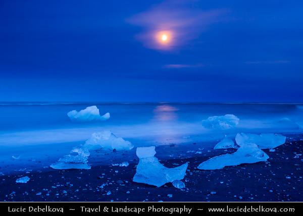 Europe - Iceland - South Eastern Iceland - Jökulsárlón Glacier Lagoon - The largest glacier lagoon at the head of the Breiðamerkurjökull glacier branching from the Vatnajökull - Pieces of Ice on the Black Sand Beach on shores of Atlantic Ocean - Dusk - Twilight - Blue Hour and the Full Moon