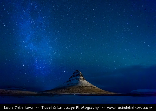 Europe - Iceland - West Iceland - Snæfell Peninsula - Snæfellsnes - Grundarfjörður - Grundarfjordur - Kirkjufell - Church Mountain (463 meters) - Iceland's most iconic pyramid shaped mountain standing isolated along the Atlantic Ocean coast at night with Aurora borealis - Northern light - Produced by solar wind particles guided by Earth's field lines to the top of the atmosphere