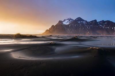Black sand beach and dunes at sunset