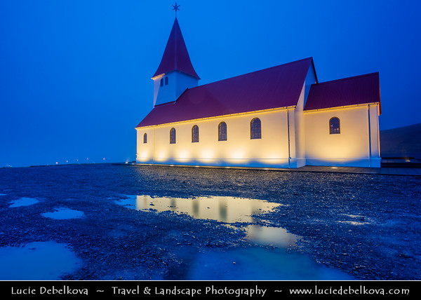 Europe - Iceland - Southernmost Iceland - Vik i Myrdal - Vík Church located high on a hill overlooking the town and famous Reynisdrangar - Basaltic columns in Atlantic Ocean
