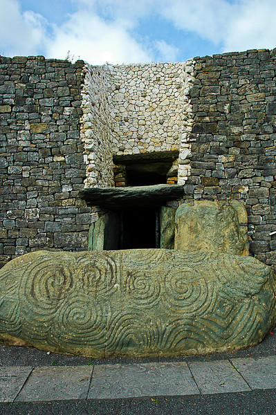 The entrance to Newgrange; the rising sun on the equinox illuminates the inner chamber through the opening above the doorway.<br /> <br /> The spiral forms on the rock are also found on the massive stoneworks at one -- but only one -- megalithic site in Brittany.
