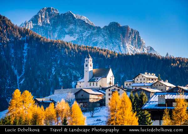 Europe - Italy - Italia - Alps - Dolomites - Dolomiti - Province of Belluno - Veneto Region - Colle Santa Lucia - Alpine area between majestic mountains of Pelmo Dolomites and Civetta - Winter time with heavy snow cover - Chiesa di Santa Lucia - Iconic church with impressive mountain backdrop