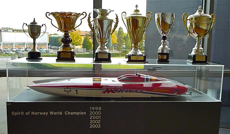 Trophies on top of a glass case with speedboat inside.