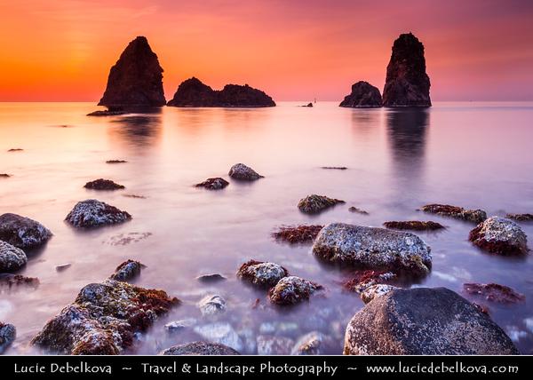 Italy - Italia - Sicily - Sicilia - Province of Catania - Aci Trezza with the typical volcanic stacks on the shores of Mediterranean sea at Sunrise