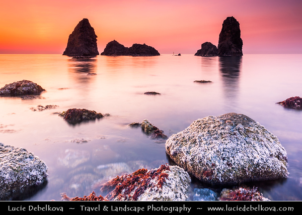 Italy - Italia - Sicily - Sicilia - Province of Catania - Aci Trezza with the typical volcanic stacks on the shores of Mediterranean sea at Sunrise