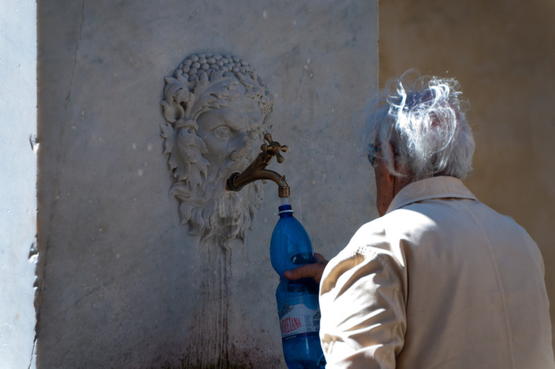 Refilling water bottles in Lucca, Tuscany, Italy