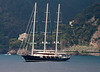 A Bermuda-rigged schooner moving out of Portofino harbor; flying something other than a Union Jack<br /> <br /> It could be the ensign of one of a number of royal yacht clubs, one of the Channel Islands or Gibraltar. I'm going with the Rock.