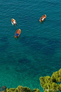 Fishing boats float on the clear azure sea off the island of Capri