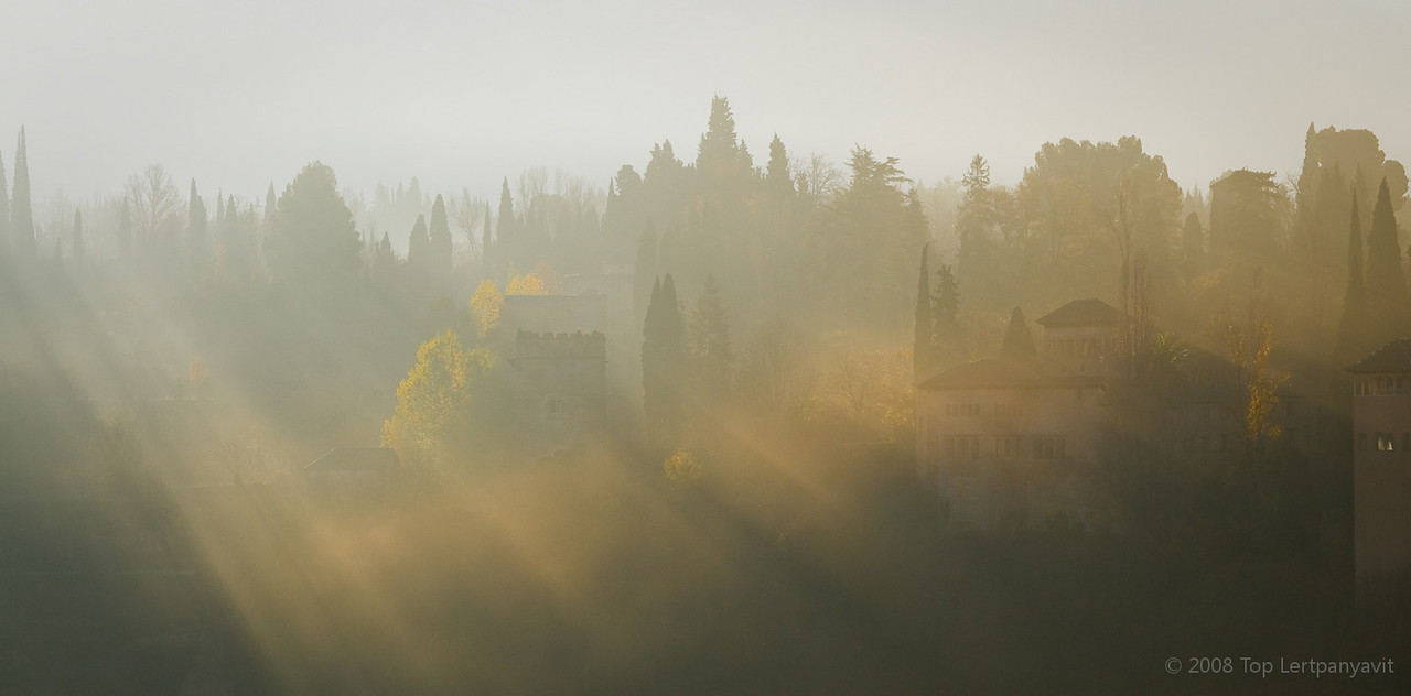 Golden morning light breaks through fog and illuminate part of the Alhambra