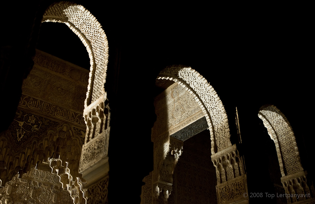 Arabesque arches illuminated by floodlights in the Alhambra at night