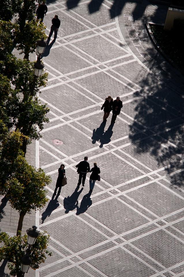 Silhouettes cast long shadows on the Plaza del Triunfo from the Giralda in Sevilla