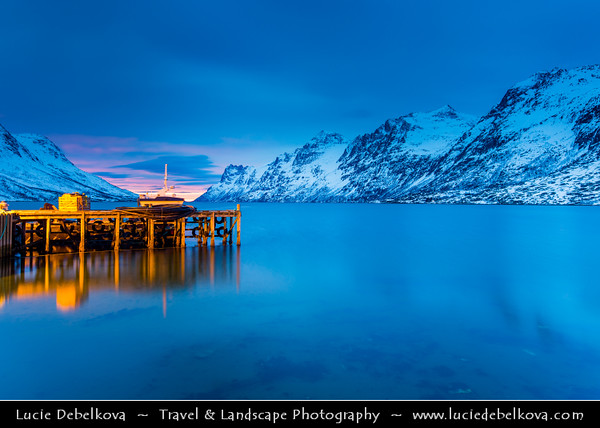 Europe - Scandinavia - Norway - North of the Arctic Circle - Troms county - Tromsø surrounding - Kvaløya island - Ersfjordbotn fishing village at the end of the Ersfjorden fjord under fresh snow during winter time at Sunset - Dusk - Twilight - Blue Hour - Night