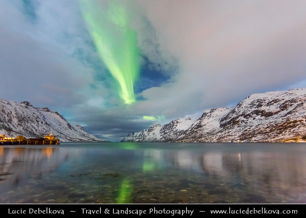 Europe - Scandinavia - Norway - North of the Arctic Circle - Troms county - Tromsø surrounding - Kvaløya island - Ersfjordbotn fishing village at the end of the Ersfjorden fjord under fresh snow during winter time with Aurora borealis - Northern light - Produced by solar wind particles guided by Earth's field lines to the top of the atmosphere