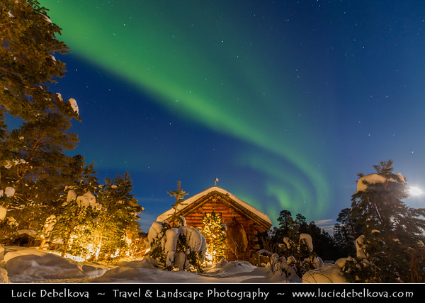 Europe - Scandinavia - Norway - Finnmark - Extreme Northeast of Norway - North of the Arctic Circle - Landscape with traditional wooden houses around Karasjok - Kárášjohka - Under snow cover during winter - Aurora borealis - Northern light - Produced by solar wind particles guided by Earth's field lines to the top of the atmosphere