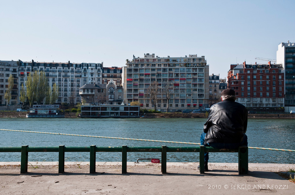 An old man sitting on the riverside