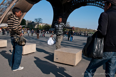 Street sellers of Tour Eiffel souvenirs discussing
